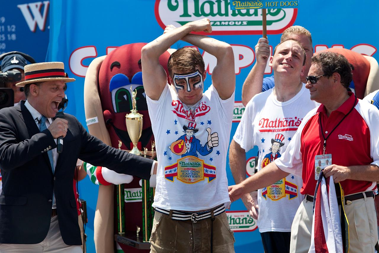 NEW YORK, NY - JULY 04:  Competitive eater Tim Janus celebrates his second place win in the men's division of the Nathan's Famous International Hot Dog Eating Contest at Coney Island on July 4, 2012 in the Brooklyn borough of New York City. Janus earned second place, with 52 hot dogs in 10 minutes, Joey Chestnut won the men's division by successfully tying his own world record by eating 68 hot dogs.  (Photo by Andrew Burton/Getty Images)