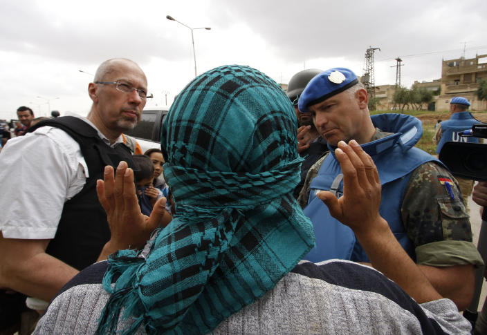 In this picture taken during UN observer-organized media tour, a Syrian man, who covers his face to obscure his identity, speaks to UN observers about conditions in Hama city, central Syria, on Thursday May 3, 2012. Syrian security forces stormed dorms at a northwestern university to break up anti-government protests there, killing at least four students and wounding several others with tear gas and live ammunition, activists and opposition groups said Thursday. (AP Photo/Muzaffar Salman)
