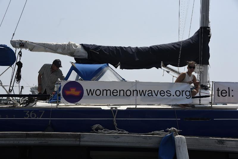 """Members of the Dutch organization Women on Waves can be seen on the group's """"abortion ship"""" as it visits the Pez Vela Marina in the port of San Jose, Escuintla department, 120 km south of Guatemala City, on February 23, 2017 (AFP Photo/JOHAN ORDONEZ)"""