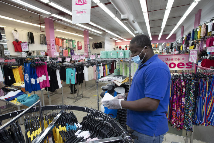 FILE - In this June 8, 2020 file photo, Danice clothing store manager Alexander Nee checks invoices as the Bronx business reopens, in New York. Restaurants, retailers and salons are desperately trying to stay afloat as the U.S. economy reopens in fits and starts after months in a coronavirus lockdown. But billions of dollars allocated by Congress as a lifeline to those very businesses are about to be left on the table when the government's Paycheck Protection Program stops accepting applications for loans Tuesday, June 29. (AP Photo/Mark Lennihan, File)
