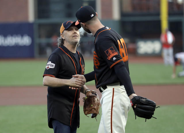 Metallica's Lars Ulrich, left, shakes hands with San Francisco Giants relief pitcher Hunter Strickland after throwing the ceremonial first pitch before a baseball game between the Giants and the Washington Nationals Monday, April 23, 2018, in San Francisco. (AP Photo/Marcio Jose Sanchez)
