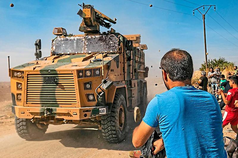 Flashpoint: Syrians throw stones at a military vehicle from Turkey — a Nato member — during a patrol near the town of Darbasiyah in north-east Syria near Turkey's border: Getty Images