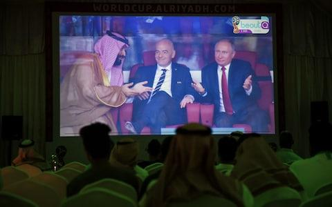 A picture taken on June 14, 2018 in a Saudi football fan tent in the capital Riyadh shows a projector showing the Russia 2018 World Cup Group A football match between Russia and Saudi Arabia, with a clip of Saudi Crown Prince Mohammed bin Salman (L) gesturing as he sits next to FIFA President Gianni Infantino (C) and Russian President Vladimir Putin - Credit: FAYEZ NURELDINE/AFP/Getty Images