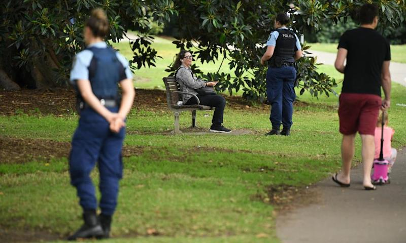 Police officers ask people sitting in parks to go home