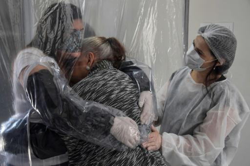 Suzane Valverde (L) hugs her 85-year-old mother Carmelita Valverde, through a transparent plastic curtain at a senior nursing home in Sao Paulo, Brazil, on June 13, 2020, amid the novel coronavirus (COVID-19) pandemic