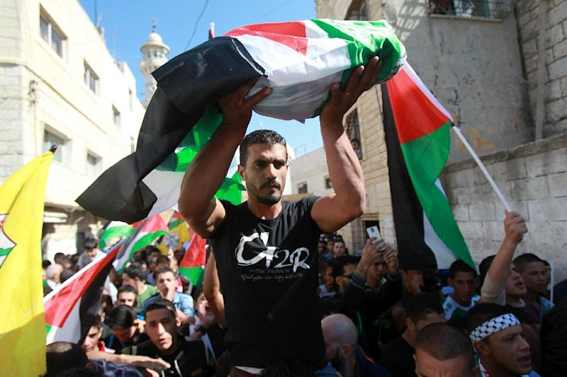 Mourners carry the body of an eight-month-old Palestinian boy, Ramadan Thawabteh, who died the previous day, during his funeral in the West Bank village of Beit Fajjar near Bethlehem on October 31, 2015