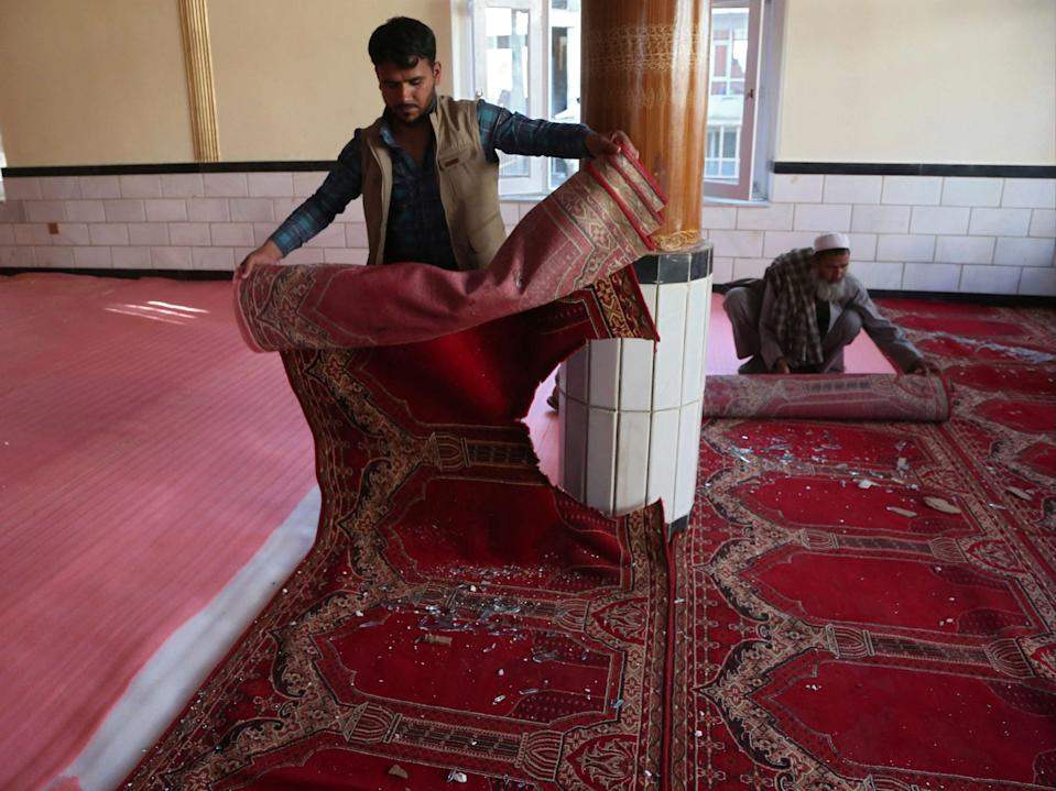 Devotees remove carpets from a mosque after a bomb blast on the outskirts of Kabul on Friday, which killed at least 12 people (AFP via Getty Images)