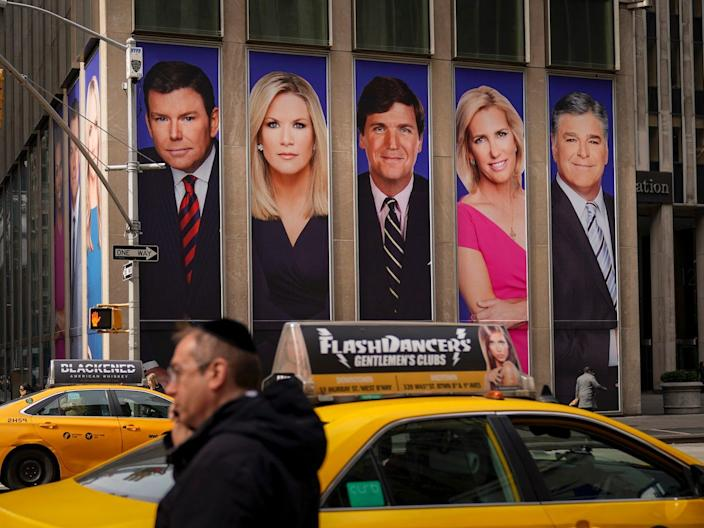 Traffic on Sixth Avenue passes by advertisements featuring Fox News personalities, in New York City, on March 13, 2019.