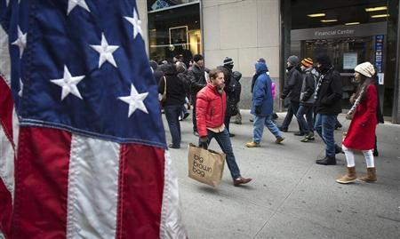 People walk along 5th Avenue as they shop for bargains the day after Christmas in New York