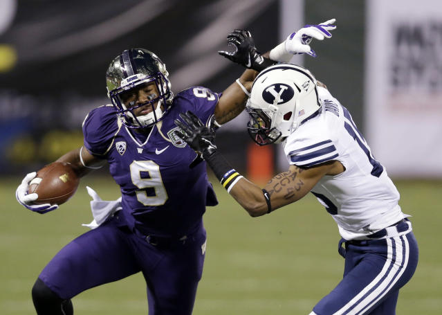 Washington's Damore'ea Stringfellow, left, tries to shake off the tackle attempt from BYU defensive back Michael Davis during first half of the Fight Hunger Bowl NCAA college football game Friday, Dec. 27, 2013, in San Francisco. (AP Photo/Marcio Jose Sanchez)