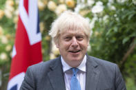 Britain's Prime Minister Boris Johnson, reacts as he walks with Australian Prime Minister Scott Morrison after their meeting, in the garden of 10 Downing Streeet, in London, Tuesday June 15, 2021. Britain and Australia have agreed on a free trade deal that will be released later Tuesday, Australian Trade Minister Dan Tehan said. (Dominic Lipinski/Pool Photo via AP)
