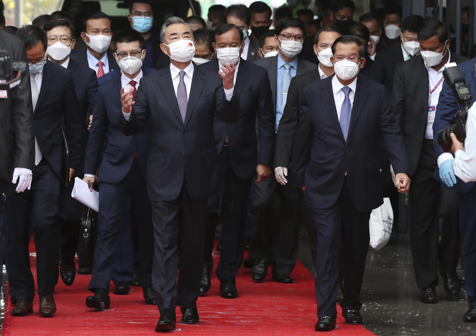 Chinese Foreign Minister Wang Yi, front left, walks with Cambodia's Prime Minister Hun Sen, front right, during a tour to the Morodok Techo National Stadium, as it was handed over to the the Cambodian organizing committee of the Southeast Asian Games, in Phnom Penh, Cambodia, Sunday, Sept. 12, 2021. Wang is visiting Cambodia, where he met with Hun Sen and other officials to discuss COVID-19 and other regional issues. (Lon Jadina/Pool Photo via AP)