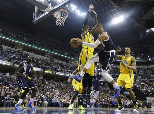 Oklahoma City Thunder's Russell Westbrook (0) passes to Kendrick Perkins (5) while defended by Indiana Pacers' Roy Hibbert (55) during the first half of an NBA basketball game on Friday, April 5, 2013, in Indianapolis. (AP Photo/Darron Cummings)