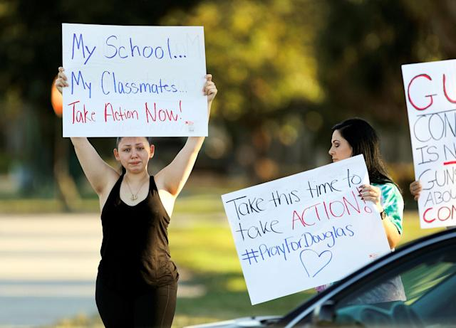 <p>Angelina Lazo (L), an 18-year-old senior at Marjory Stoneman Douglas High School, who said that she lost two friends in the shooting at her school two days ago, reacts to honks of support from passing motorists as she and her mother, Linda Lazo (R), join other gun control proponents with placards at a street corner in Coral Springs, Fla., Feb. 16, 2018. (Photo: Jonathan Drake/Reuters) </p>