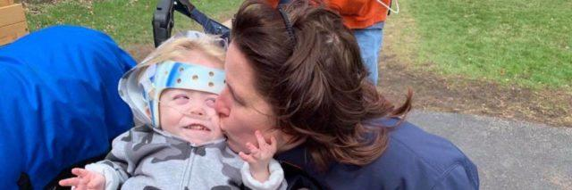 Jennifer Daly kissing her son as he grabs her face and smiles. He is sitting on his wheelchair.