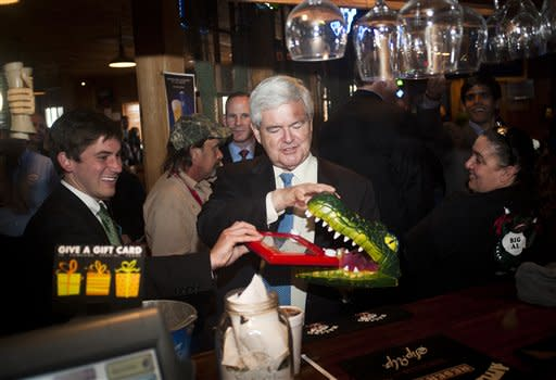 Republican presidential candidate Newt Gingrich holds an Etch A Sketch in the mouth of a plastic alligator head at Big Al's Seafood Restaurant on Thursday, March 22, 2012 in Houma, La. (AP Photo/The Houma Daily Courier, Michael Conti)