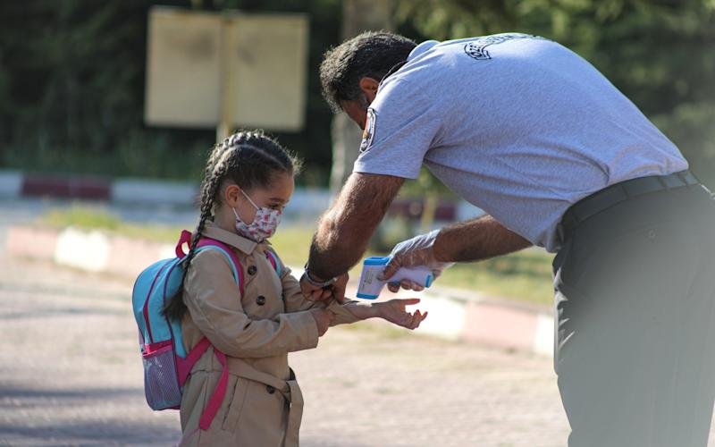 A school security clerk checks body temperature of a student at the school yard - Ayhan Iscen/Anadolu Agency via Getty Images