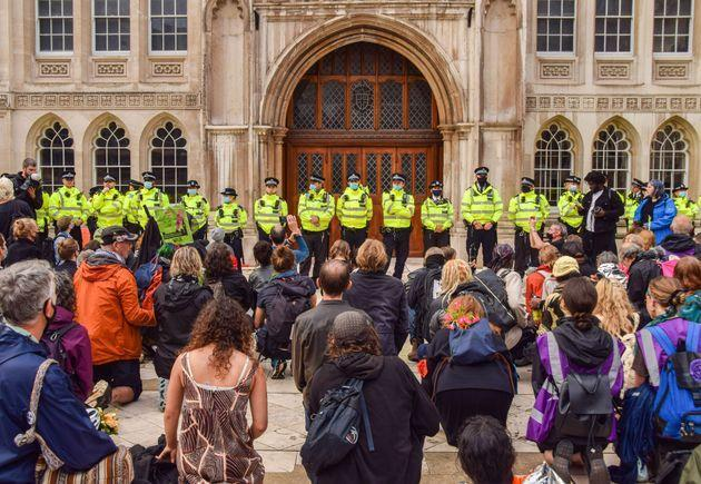 Protesters kneel down while police officers guard the Guildhall building entrance during the demonstration (Photo: SOPA Images via Getty Images)
