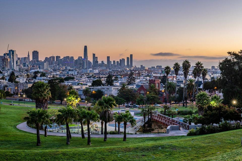 sun rises over the San Francisco skyline from Mission Dolores Park