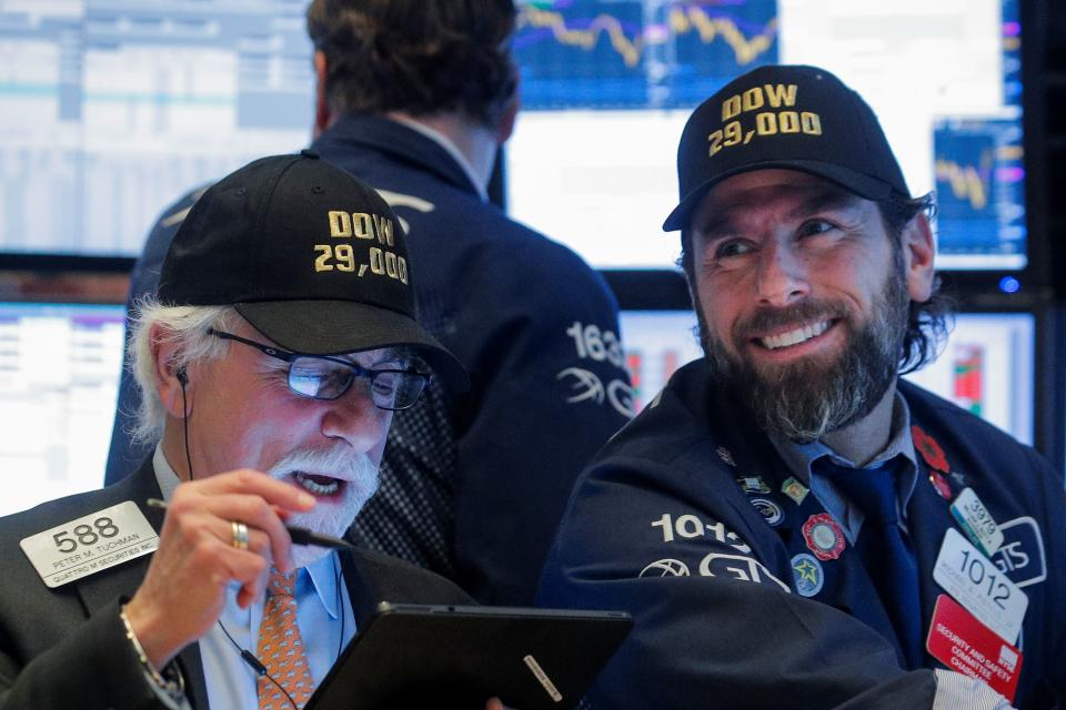 Trader Peter Tuchman and specialist trader Michael Pistillo wear DOW 29,000 hats on the floor at the New York Stock Exchange (NYSE) in New York, U.S., January 15, 2020. REUTERS/Brendan McDermid