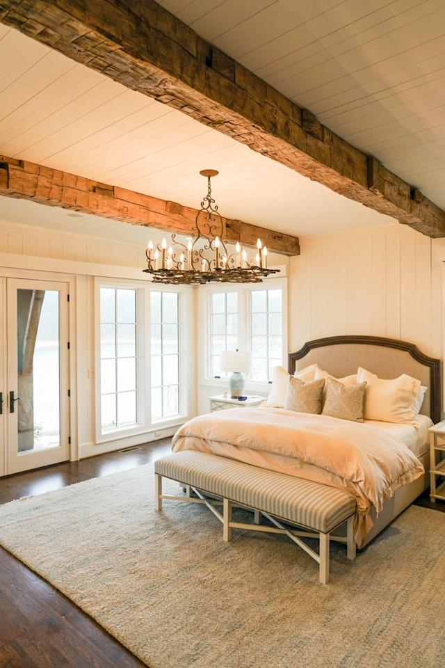 """<p>Sophisticated neutrals are used throughout this charming bedroom, designed by <a href=""""https://deringhall.com/specialty-artisans/evolutia"""">Evolutia</a>. The traditional chandelier and hand-hewn beams give the space a country style.</p>"""