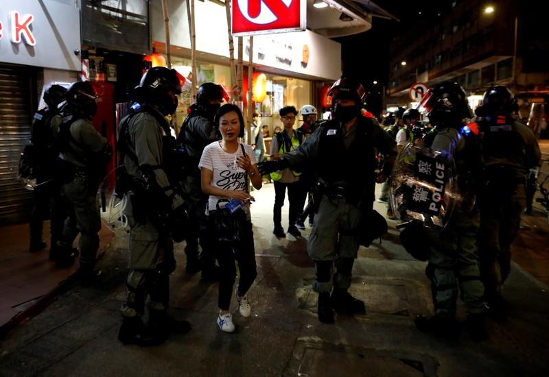 Riot police ask a woman to detour as they disperse pro-democracy demonstrators gathering to commemorate the three-month anniversary of an assault by more than 100 men on protesters, commuters and journalists, in Hong Kong