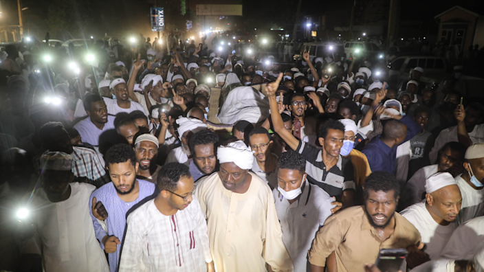 Crowds gather at night holding phones to provide light at the funeral of Zubair Ahmed al-Hassan, the secretary general of the Islamic Movement in Khartoum, Sudan - Saturday 1 May 2021