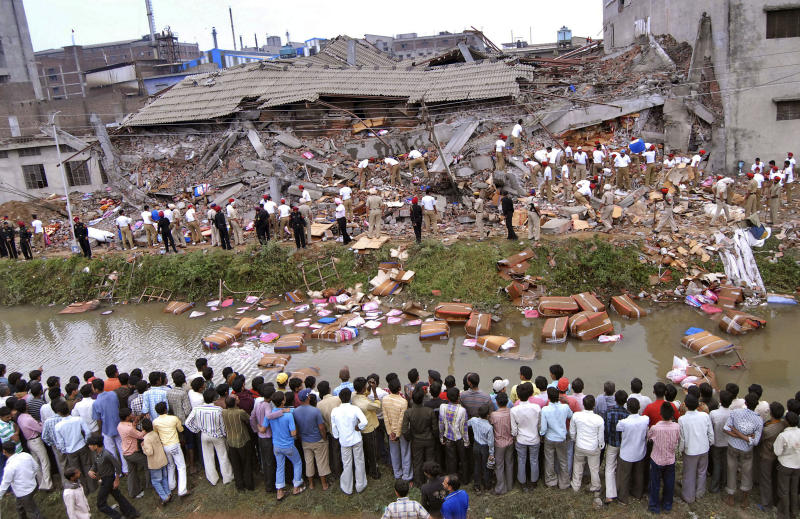 Workers and residents watch rescue operations at the site of a collapsed factory in Jalandhar, India, Monday, April 16, 2012. Several people are feared to be trapped after a three-story building of a factory collapsed after a blast in the factory's boiler, according to local reports. (AP Photo/Altaf Qadri)