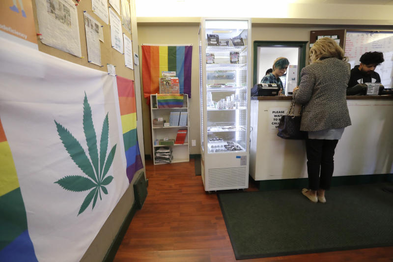 In this Wednesday, Oct. 9, 2019 photo, clerks assist a customer at the Medicinal Cannabis Dispensary, an unlicensed marijuana shop, in Vancouver, B.C. In Vancouver, which has 2.2 million residents and is Canada's third-largest city, there was tacit approval of marijuana even before legalization. (AP Photo/Elaine Thompson)