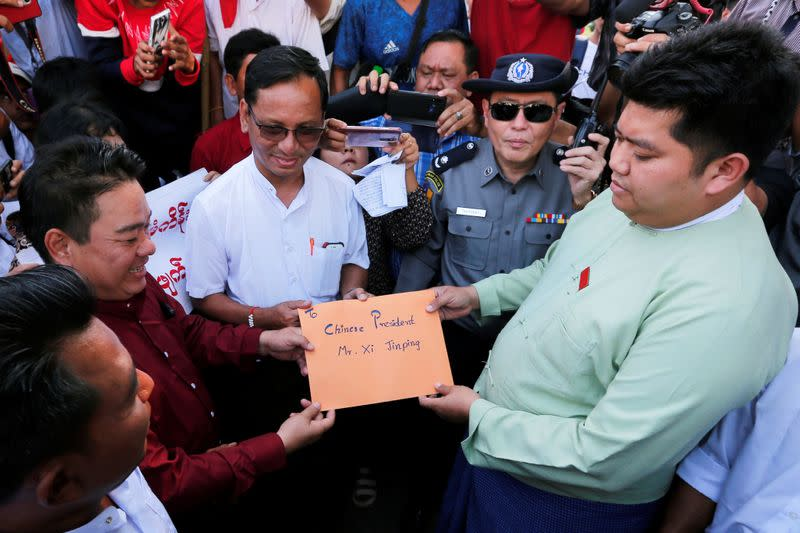 Protesters hold a letter addressed to Chinese President Xi Jinping against Myitsone hydropower dam during the last day of his visit in Yangon