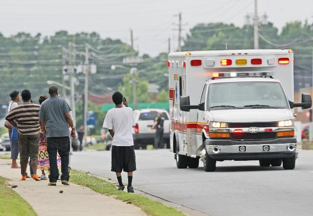 People watch as an ambulance drives off after a shooting occurred on Friday, June 21, 2013 in Greenville, N.C. A man armed with a shotgun wounded one person at a North Carolina law firm Friday before crossing a busy street and entering a Wal-Mart, where he shot three more people before officers subdued him, police said. Greenville Police Chief Hassan Aden said the suspect was shot by officers at the entrance of the store. He didn't have the conditions of those shot and didn't have a motive. (AP Photo/The Daily Reflector, Aileen Devlin)