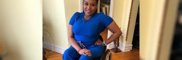 Andrea Dalzell in her blue nurse's uniform, sitting in her wheelchair.