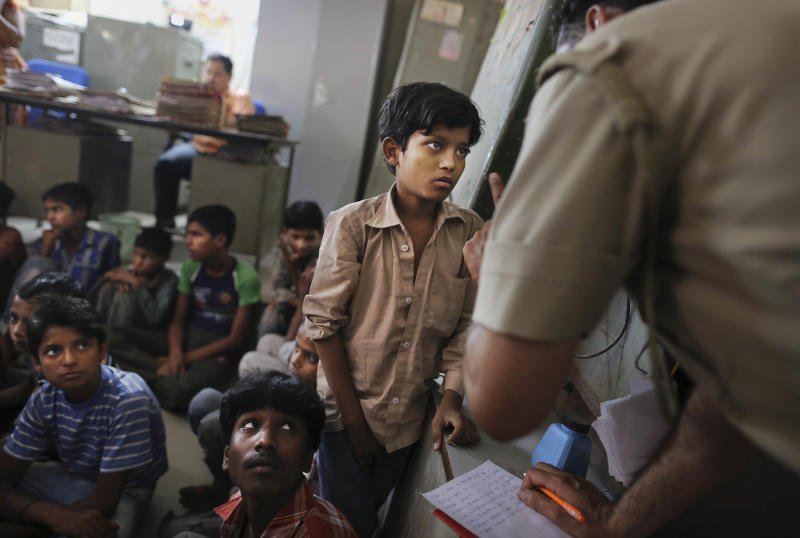 A young Indian bonded child laborer gives details to a police officer at the district magistrates office after being rescued during a raid by workers from Bachpan Bachao Andolan or Save the Childhood Movement, at a garment factory in New Delhi, India, Tuesday, June 12, 2012. Police raids on factories in the Indian capital revealed dozens of migrant kids hard at work Tuesday despite laws against child labor. Police rounded up 26 children from three textiles factories and a metal processing plant, but dozens more are believed to have escaped. Those captured had all come to New Delhi from the states of Bihar and Uttar Pradesh. (AP Photo/Kevin Frayer)