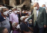 Turkey's President Recep Tayyip Erdogan speaks with villagers in front of a wildfire-destroyed house in Manavgat, Antalya, Turkey, Saturday, July 31, 2021. The death toll from wildfires raging in Turkey's Mediterranean towns rose to six Saturday after two forest workers were killed, the country's health minister said. Fires across Turkey since Wednesday burned down forests, encroaching on villages and tourist destinations and forcing people to evacuate.(Turkish Presidency via AP, Pool)