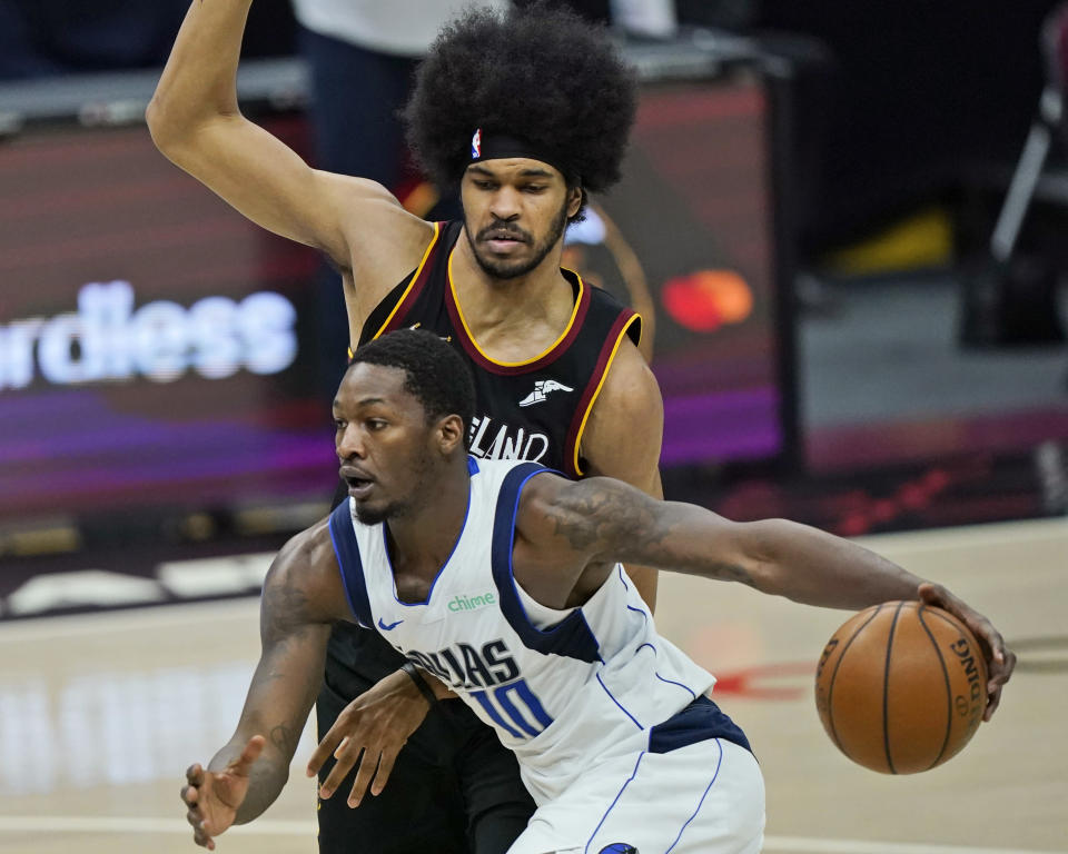 Dallas Mavericks' Dorian Finney-Smith, front, drives against Cleveland Cavaliers' Jarrett Allen during the second half of an NBA basketball game Sunday, May 9, 2021, in Cleveland. Dallas won 124-97. (AP Photo/Tony Dejak)