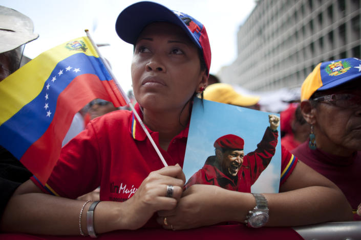 """A woman holds a picture of Venezuela's President Hugo Chavez and the country's national flag during an event commemorating the violent street protests of 1989 known as the """"Caracazo,"""" in Caracas, Venezuela, Wednesday, Feb. 27, 2013. The wave of the 1989 violent protests, seen by the Chavez government as a """"popular uprising,"""" was in response to the economic measures imposed by then President Carlos Andres Perez. (AP Photo/Ariana Cubillos)"""