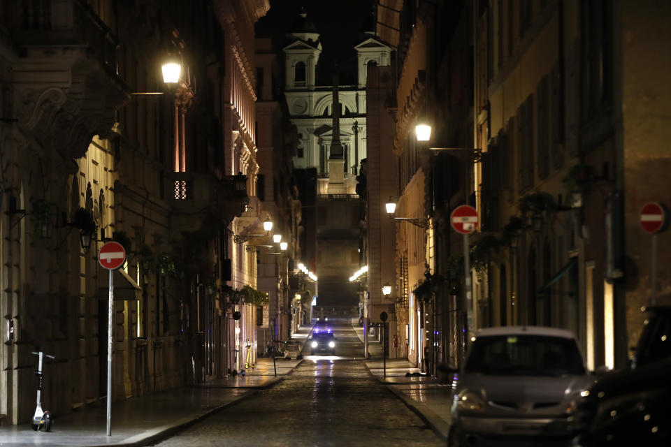 An Italian Carabinieri paramilitary police car patrols an empty street leading to the Spanish Steps and Trinita' dei Monti Church Rome, early Monday, Oct. 26, 2020. Since midnight last Friday and for the next 30 days, people in Lazio are not allowed to leave their homes from midnight to 5 a.m. daily, except to go to or return from work or for other urgent reasons such as health issues. (AP Photo/Alessandra Tarantino)