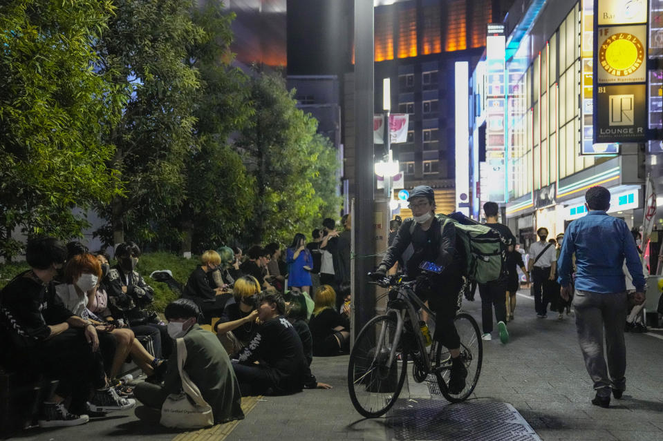 People walk around and gather at a bar after government imposed 8 p.m. closing time for restaurants and bars under Tokyo's fourth state of emergency Saturday, July 17, 2021, in Tokyo. The latest state of emergency has asked restaurants and bars to close by 8 p.m., if not entirely. This has pushed people to drink outside, although many bars remain open and bustling with customers who are defying the rules and expressing frustration and indifference. (AP Photo/Kiichiro Sato)
