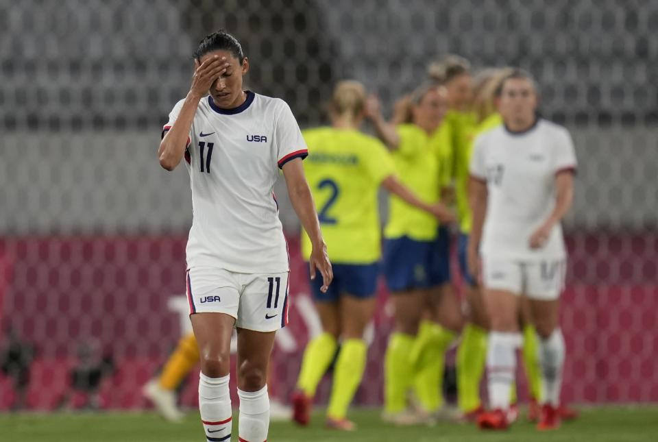 United States' Christen Press reacts as Sweden's players celebrate their third goal during a women's soccer match at the 2020 Summer Olympics, Wednesday, July 21, 2021, in Tokyo. (AP Photo/Ricardo Mazalan)