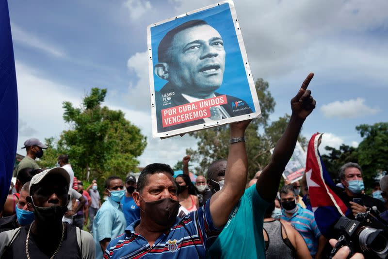People shout slogans in support of the government as Cuba's President Miguel Diaz-Canel talks to the media, in San Antonio de los Banos