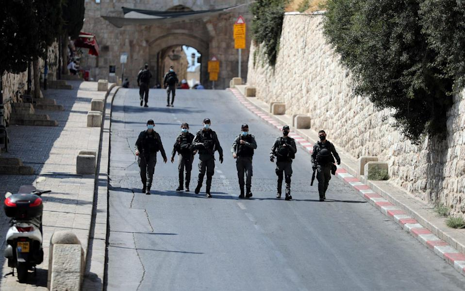 Israeli security forces walk by the entrance to Lions Gate in Jerusalem - Reuters