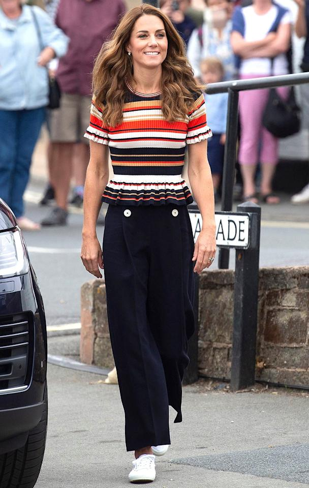"""The Duchess of Cambridge arrived to <a href=""""https://people.com/royals/kate-middleton-prince-william-compete-charity-sailing-race/"""" target=""""_blank"""">The King's Cup Regatta charity sailing race</a> wearing a very chic, nautical-style outfit. Kate paired a colorful striped peplum top by <a href=""""https://click.linksynergy.com/deeplink?id=93xLBvPhAeE&mid=1237&murl=https%3A%2F%2Fshop.nordstrom.com%2Fsr%3Forigin%3Dkeywordsearch%26amp%3Bkeyword%3Dsandro%2Bfor%2Bwomen%26amp%3Btypein%3Dsandro%26amp%3Bposition%3D2&u1=PEO%2CShopping%3AEverythingYouNeedtoCopyKateMiddleton%E2%80%99sSummerStyle%2Ckamiphillips2%2CUnc%2CGal%2C7115494%2C201908%2CI"""" target=""""_blank"""" rel=""""nofollow"""">Sandro</a> with navy culottes by L.K. Bennett and rocked <a href=""""https://people.com/style/kate-middleton-superga-sneakers-amazon/"""" target=""""_blank"""">her beloved white Superga sneakers</a> before changing into her sailing attire.  <strong>Get the Look!</strong>  Madewell Whisper Crew Tee, $16.25 (orig. $25); <a href=""""https://click.linksynergy.com/deeplink?id=93xLBvPhAeE&mid=42352&murl=https%3A%2F%2Fwww.shopbop.com%2Fwhisper-crew-neck-tee-madewell%2Fvp%2Fv%3D1%2F1542817514.htm&u1=PEO%2CShopping%3AEverythingYouNeedtoCopyKateMiddleton%E2%80%99sSummerStyle%2Ckamiphillips2%2CUnc%2CGal%2C7115494%2C201908%2CI"""" target=""""_blank"""" rel=""""nofollow"""">shopbop.com</a>  Romwe Women's Ruffle Hem Striped Short Sleeve Peplum Top Blouse, $16.99; <a href=""""https://www.amazon.com/Romwe-Womens-Ruffle-Striped-Sleeve/dp/B07QGVQ2ZL/ref=as_li_ss_tl?keywords=short+sleeve+striped+peplum+tops+for+women&qid=1565624809&s=gateway&sr=8-2&linkCode=ll1&tag=poshoppingkatemiddletonsummerstylekphillips819-20&linkId=7cd9e510231dc1594a9dd0defd89d30e&language=en_US"""" target=""""_blank"""">amazon.com</a>  J.Crew Rainbow Stripe Ruffle Strap Tank Sweater, $59.50; <a href=""""https://click.linksynergy.com/deeplink?id=93xLBvPhAeE&mid=1237&murl=https%3A%2F%2Fshop.nordstrom.com%2Fs%2Fj-crew-rainbow-stripe-ruffle-strap-tank-sweater%2F5268107&u1=PEO%2CShopping%3AEverythingYou"""