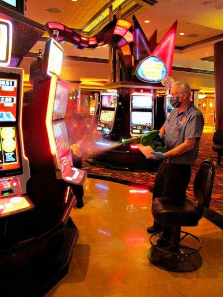 PHOTO: Steven Ford, a worker at Harrah's casino sprays slot machines with disinfectant in Atlantic City, N.J., July 1, 2020, as the casino prepared to reopen. (Wayne Parry/AP)