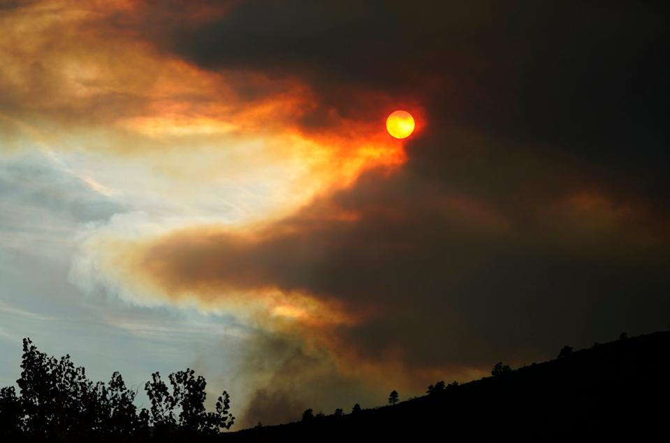 Smoke obscures the sun as fire approaches a ridge along Highway 36 as several wildfires burn in the state Wednesday, Oct. 21.