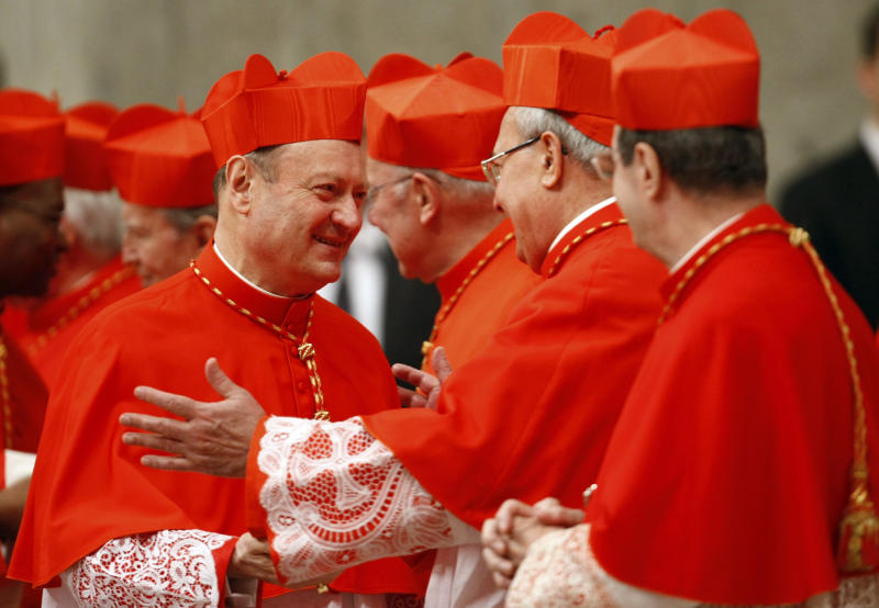 FILE -- In this file photo taken at the Vatican on Nov. 20, 2010, Cardinal Gianfranco Ravasi, left, is congratulated by Cardinal Angelo Sodano, second from right, after being elevated by Pope Benedict XVI during a consistory inside St. Peter's Basilica. He looks to Amy Winehouse for inspiration and, unlike Benedict XVI, actually taps out his tweets himself. Cardinal Gianfranco Ravasi is an erudite scholar with a modern touch _ and that is seen by some as just the combination the Catholic Church needs to revive a church beset by scandal and a shrinking flock. (AP Photo/Pier Paolo Cito)
