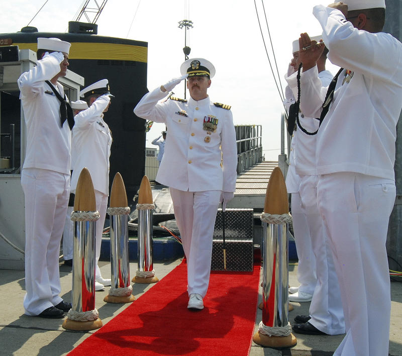 In this Aug. 3, 2012 photo provided by the U.S. Navy, Cmdr. Michael P. Ward II, center, is saluted during the change-of-command ceremony for the nuclear submarine USS Pittsburgh at the Naval Submarine Base New London, in Groton, Conn.  Ward was relieved of his command in August 2012 after he faked his own death to end an affair with a woman. Ward's lawyer said Friday, April 12, 2013, during a hearing in Groton to determine his status with the Navy, that Ward admits to the mistake and apologizes, and that he should not be expelled from the Navy. (AP Photo/U.S. Navy, Jason J. Perry )