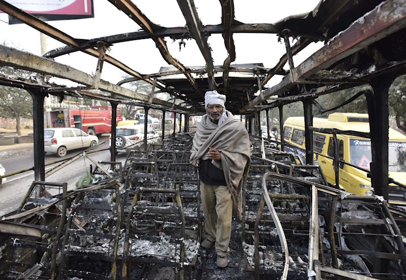 "A bus conductor stands inside a bus that was set on fire near the village of Bhondsi in Gurgaon, allegedly by activists of Karni Sena, who were protesting against the release of film ""Padmaavat.""  (Hindustan Times via Getty Images)"