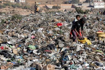 A woman carrying a child collects salvageable items at the Andralanitra garbage dump in Antananarivo