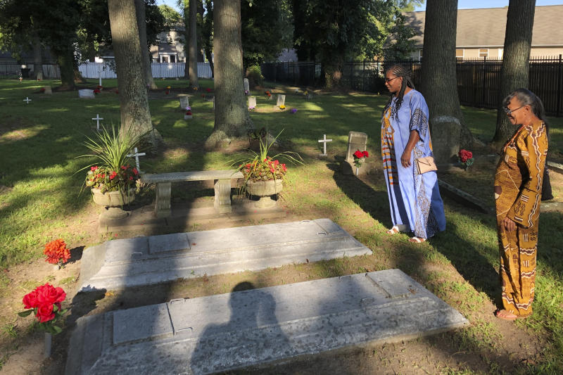 Earline Jackson, right, and Phyllis Bradshaw stand at a relative's grave in the Tucker Family Cemetery in Hampton, Va. on Friday, Aug. 23, 2019. They are part of a larger family that traces its roots to first enslaved Africans to arrive in Virginia in 1619. (AP Photo/Ben Finley)