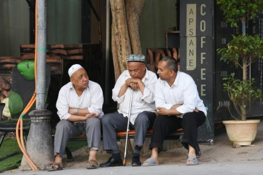 Members of China's Uighur minority outside a coffee bar in the restored old city area of Kashgar, a tourist magnet just a stone's throw from internment camps